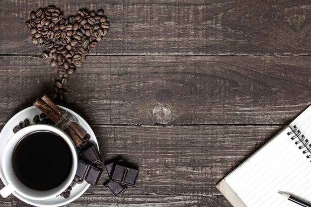 Taza de café y frijoles en forma de corazón con canela, chocolate y cuaderno en blanco