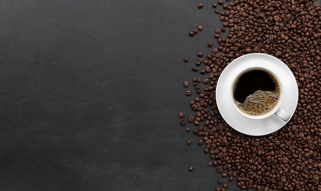Taza de café y frijoles en la mesa de madera negra