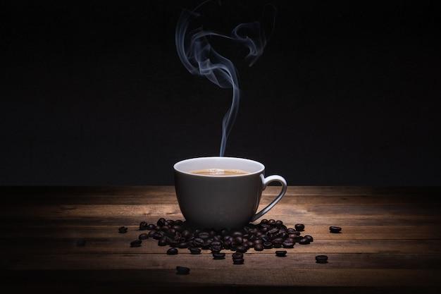 Una taza de café y frijoles en la mesa de madera