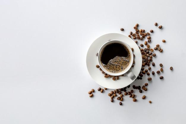 Taza de café y frijoles sobre fondo blanco de mesa. vista superior