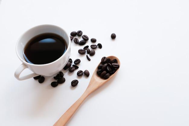 Taza de café y frijoles sobre un fondo blanco.