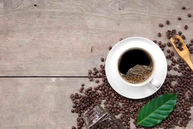 Taza de café y frijoles sobre fondo de piso de madera. vista superior