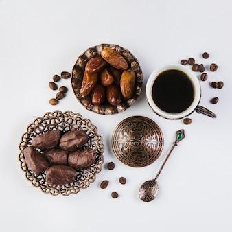 Taza de café con frutas de fechas en la mesa
