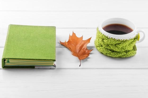 Una taza de café fuerte y un cuaderno. el concepto de otoño, naturaleza muerta, relajación, estudio.
