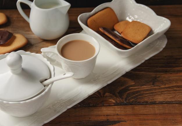 Taza de café y galletas en una bandeja en la mesa de madera de cerca
