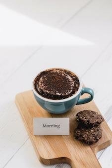 Taza de café con galletas de chocolate negro y mensaje de saludo en bandeja de madera en cafe