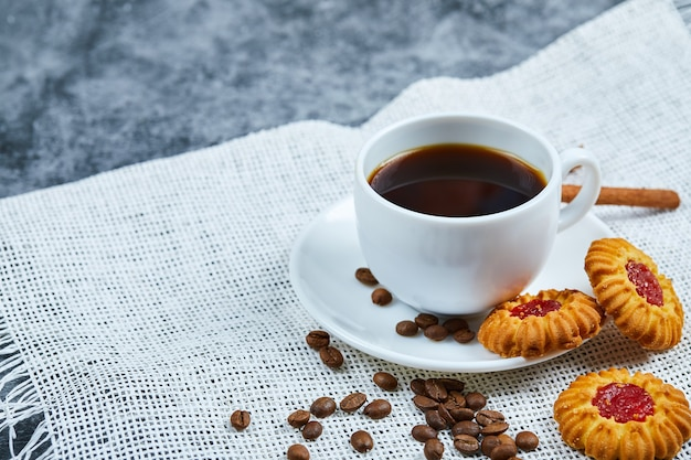 Una taza de café, galletas, granos de café y canela.