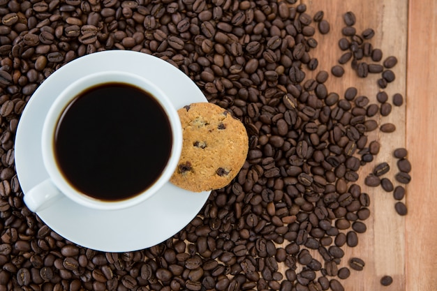 Taza de café con galletas y granos de café.