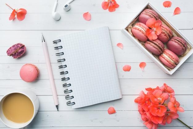 Taza de café, galletas de macarrones en una caja, flores y un cuaderno de notas planas.