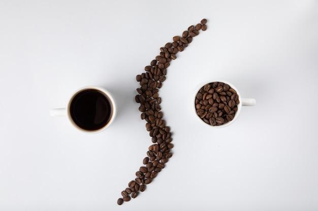 Taza de café con granos de café aislados en blanco