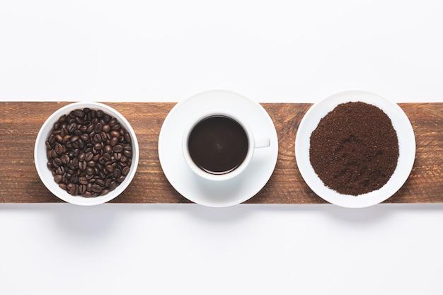 Taza de café, granos de café y café molido.
