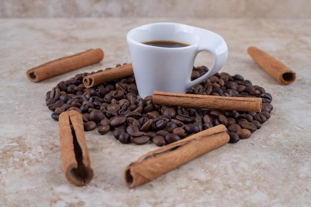 Una taza de café, granos de café y canela en rama.