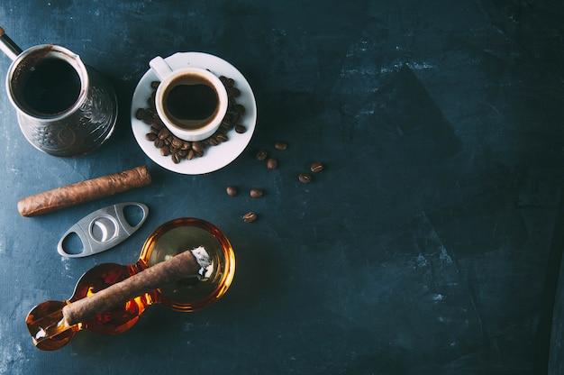 Taza de café, granos de café, cenicero con cigarro oscuro