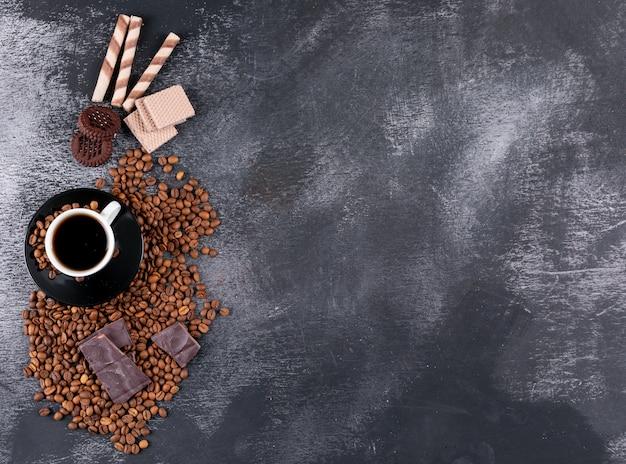Taza de café con granos de café, chocolate y galletas con espacio de copia