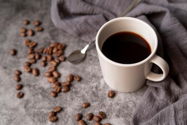 Taza de café con granos de café y cuchara.