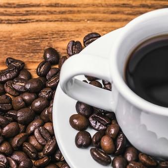 Una taza de café y granos de café dispersos.