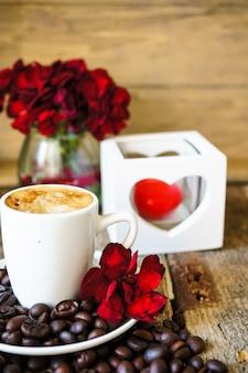 Taza de café con granos de café y flores