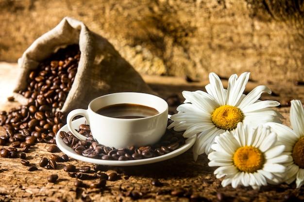 Taza de café y granos de café fritos en una mesa de madera con hermosas flores blancas sobre un fondo de madera