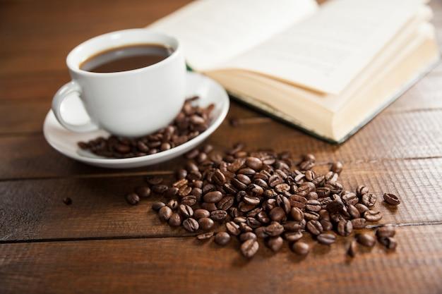 Taza de café con granos de café y el libro
