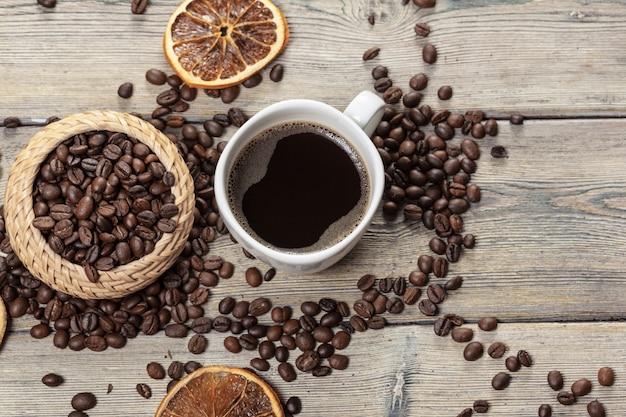 Taza de café y granos de café en madera.