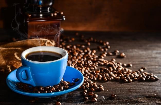 Taza de café con granos de café y molinillo de fondo