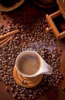 Taza de café y granos de café en un saco sobre fondo oscuro, vista superior