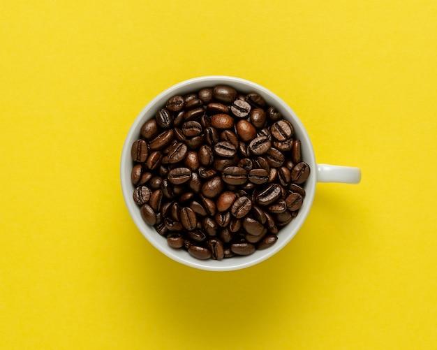 Taza de café con granos de café sobre fondo amarillo