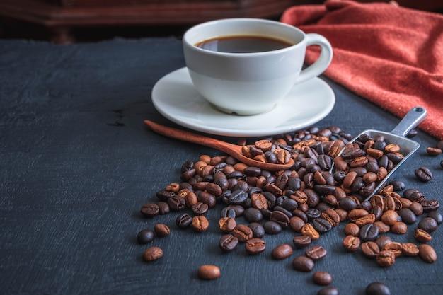 Taza de café y granos de café sobre fondo negro
