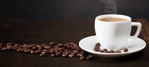 Taza de café y granos de café sobre la mesa. fondo negro.