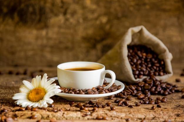 Taza de café y granos de café sobre una mesa de madera con manzanilla