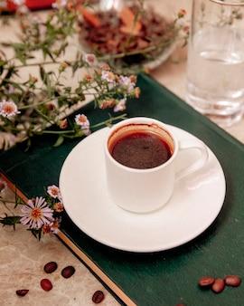 Taza de café y granos de café sobre la mesa