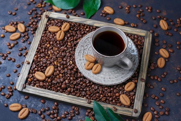 Una taza de café con granos de café tostados y galletas con forma de grano de café sobre una superficie oscura