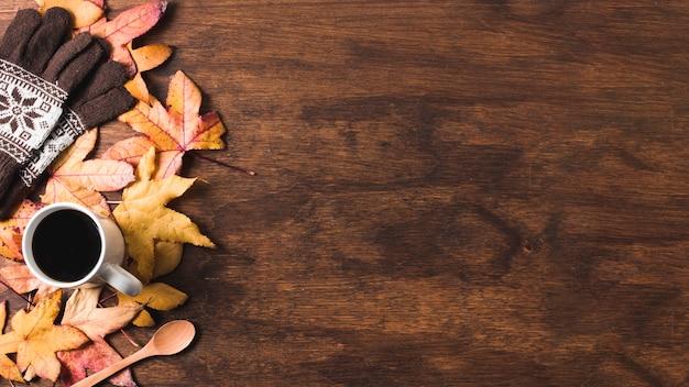 Taza de café y guantes en hojas de otoño copia espacio