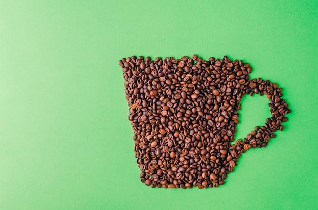 Taza de café hecha de granos de café sobre un fondo verde, perfecta para un fondo de pantalla genial