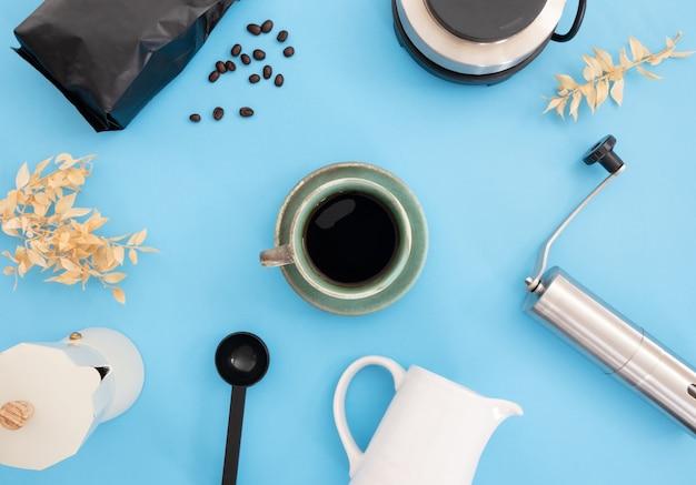 Taza de café y herramientas para hacer café sobre fondo azul claro