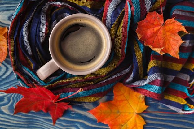 Taza de café, hojas de otoño y una cálida bufanda en la superficie de la mesa de madera negra
