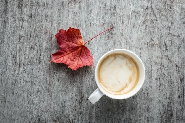 Una taza de café y hojas de otoño en una mesa de madera