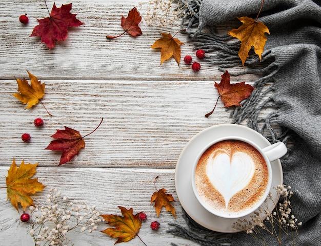 Taza de café y hojas secas sobre fondo blanco de madera. endecha plana, vista superior, espacio de copia