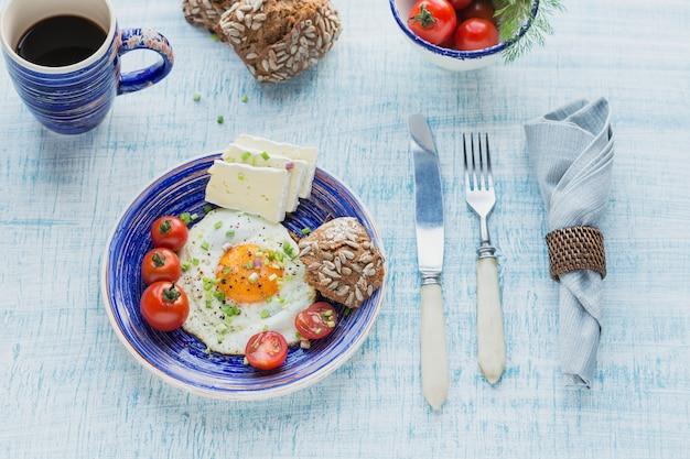 Taza de café, un huevo, queso y tomates cherry para un desayuno saludable.