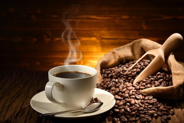 Taza de café con humo y granos de café sobre fondo de madera vieja