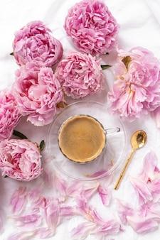 Taza de café instantáneo en la mesa con peonías rosas bajo las luces