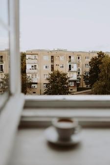 Una taza de café junto a la ventana.