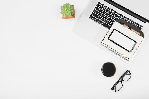 Taza de café con laptop; teléfono celular y diario con pluma sobre fondo blanco