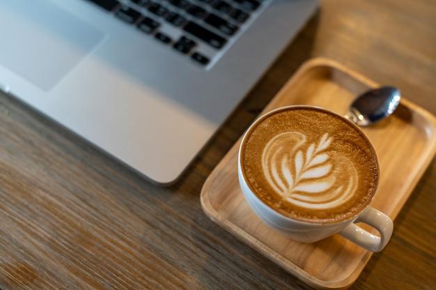 Taza de café latte art con computadora portátil en la mesa
