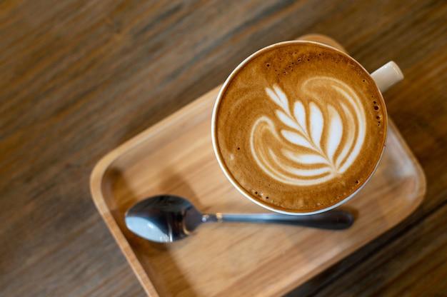 Taza de café latte art con cucharas en placa, endecha plana