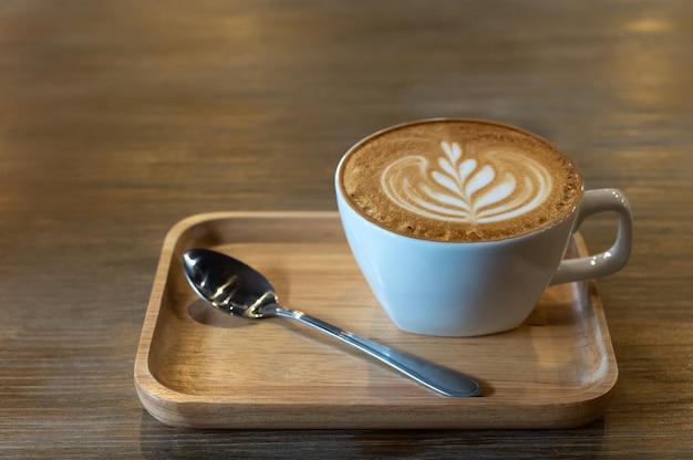 Taza de café latte art con cucharas en placa