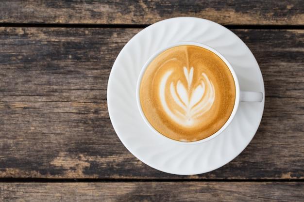 Taza de café latte art en madera