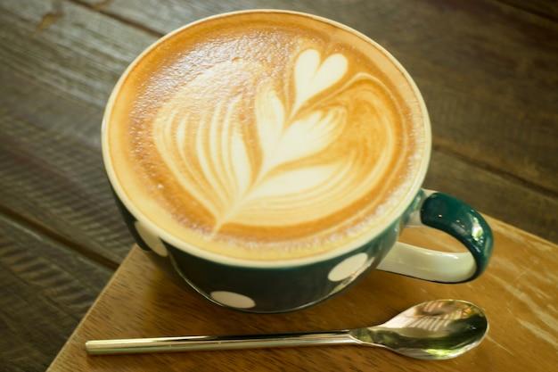 Taza de café latte art en mesa de madera