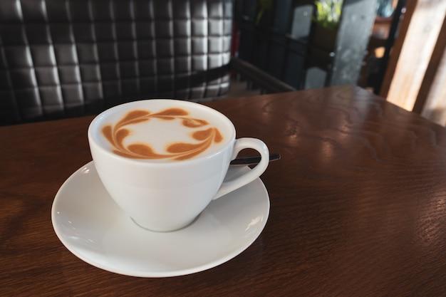 Taza de café latte en la mesa de madera en café.