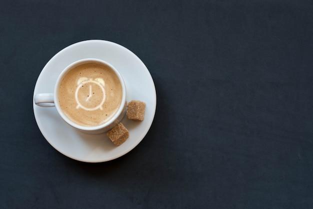 Taza de café con leche, azúcar de caña y reloj despertador firmar sobre fondo oscuro. vista superior. copia espacio